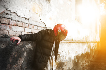 Photo of a biker. Young boy in red helmet and black jacket. Cool guy.
