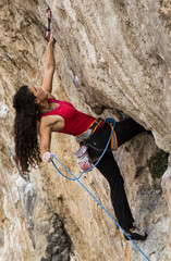 A woman ready to clip while she is climbing at the Jurassic Park sector in Kalymnos, Greece.