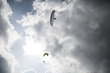 Two paraglider in the sky in front of fuzzy clouds. Wasserkuppe, Rhoen Mountains, Germany