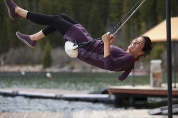 A woman on a swing on a dock.