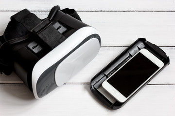 virtual reality glasses with smartphone on wooden background