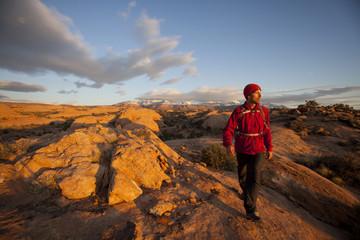 Young man hiking on slickrock near Moab, Utah.