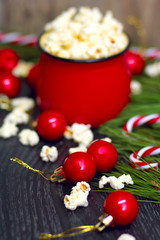 Salty fresh crusty homemade popcorn in red cup in the fashion black background in a New Year's interior with red Christmas balls.