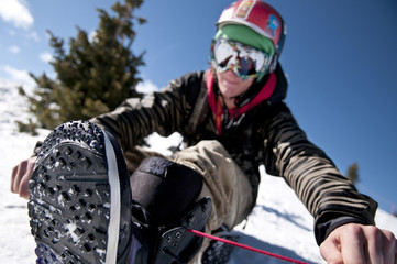A snowboarder wearing goggles and a helmet sits on the side of a mountain and ties his snowboard boots.