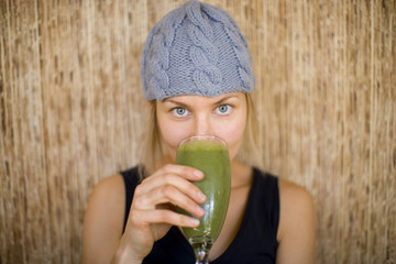 Portrait of woman drinking a green smoothie and making a green mustache with the beverage.