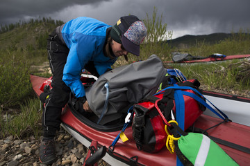 A woman unloads her kayak in preparation for camping on the shore of the Onon River in northern Mongolia.