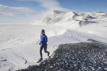 Woman trail running on Hut Point Peninsula on Ross Island, Antarctica.