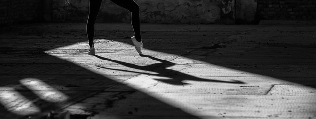 Young modern ballet dancer exercising and dancing in abandoned building