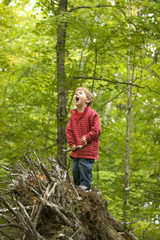 Young boy playing in forest in forest in rural Lake Ossipee, New Hampshire.