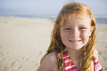 A smiling young girl enjoys a sunny summer afternoon at the beach in Huntington Beach, California.