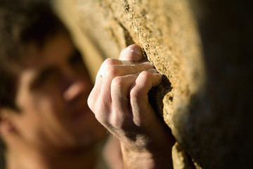 Climber grimacing as he grips onto hold