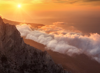 Wall Mural - Mountain landscape at sunset. Amazing view from the mountain peak on rocks, low clouds, blue sky and sea in the evening. Colorful nature background. Adventure. Travel in Crimea. Beautiful scenery
