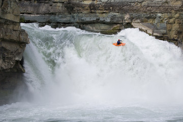 Young man kayaking over Fernie Falls on lower Elk River near Fernie, BC, Canada.