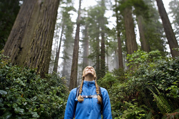 A woman in a blue fleece hiking in a lush green forest.