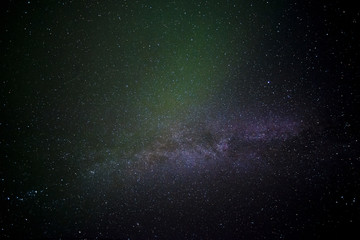 The Aurora Borealis flares briefly over the Milky Way in Iceland.