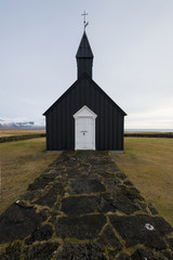 The iconic Budir Black Church of Iceland and the black cobblestone that leads up to it.