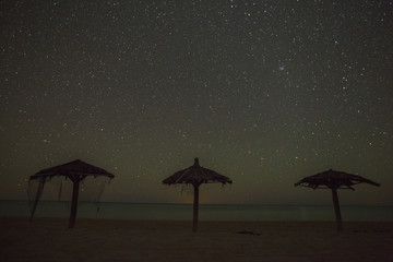 Nighttime image of palapas with stars.