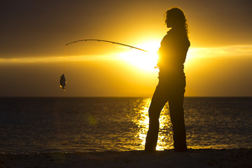 The silhouette of a female angler holding a fishing poll and her catch of the day as the sun sets over the Caribbean Sea in Belize.