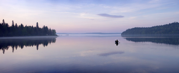 a man paddles a canoe at dawn on May 27, 2015 on Allagash Lake in northern Maine. Allagash Lake is part of the Maine Allagash Wilderness Waterway State Park.