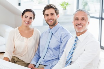 Portrait of business colleagues sitting at desk