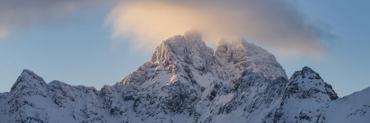 Clouds light up in winter sun over Gjerdtindan mountain peaks, Moskenesøy, Lofoten Islands, Norway