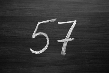number fifty seven enumeration written with a chalk on the blackboard