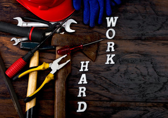 Tools and work hard written with letters on the wooden table which represent the popular phrase as lifestyle concept. Selective focus and small depth of field.