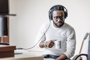 Artist producing music in his home sound studio.