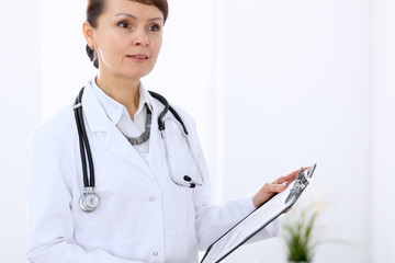 Happy female doctor standing in hospital. Medicine and health care concept.