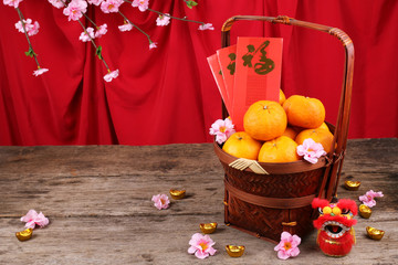 Basket of mandarin oranges with Chinese new year red packets