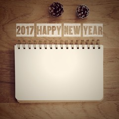 2017 happy new year words and blank note book paper on wood