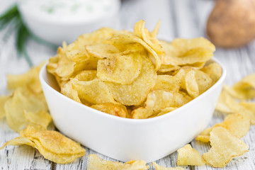 Portion of Potato Chips with Sour Cream taste on wooden backgrou