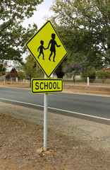 black and yellow School sign with fenced schoolground in background