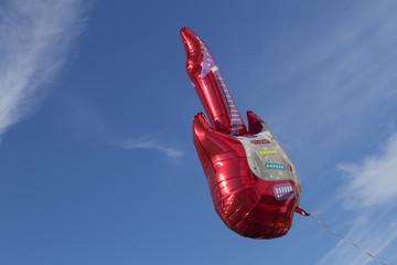 Ein roter Luftballon in Form einer elektrischen Gitarre schwebt im blauen Himmel.