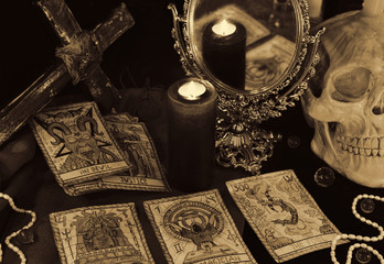 Magic still life with the Tarot cards, mirrow and skull in sepia tone