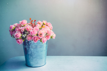 Stii life of pink rose bouquet in pot on table. Vintage filtered