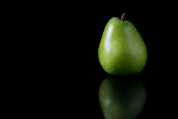 Reflecting green pear on a black background