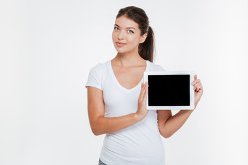 Woman holding digital tablet and showing the display