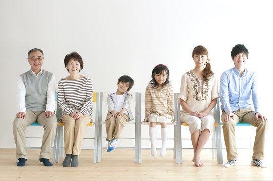 椅子に座る3世代家族