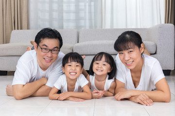 Happy Asian Chinese parents and daughters lying on the floor