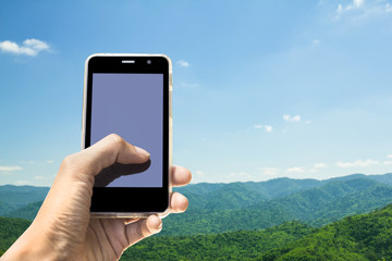 Hands Mobile Phone and mountains nature background.