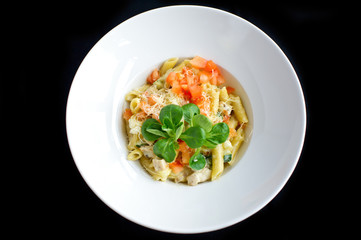 pasta with vegetables and cheese in white plate and black background