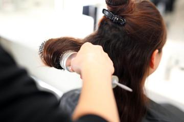 Modelowanie włosów na szczotkę. Kobieta u fryzjera, fryzjer modeluje włosy na okrągłej...