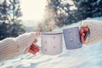 Man and woman hands in knitting mittens with cups of hot tea on