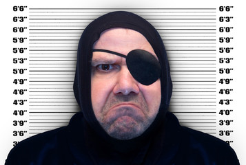 Portrait of a man with the eyepatch on background mugshot