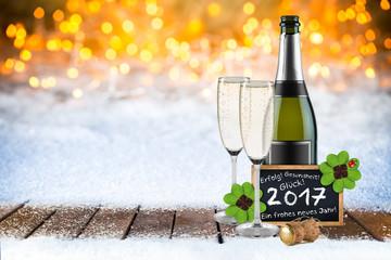 2017 Silvester bokeh Hintergund mit Sektflasche Sektgläsern Tafel mit Grüßen und Wünschen im Schnee auf Holzboden