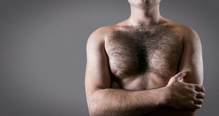 Man with hairy chest isolated on gray background for text.