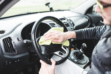Mature male with glasses cleaning car dashboard with a yellow cloth.