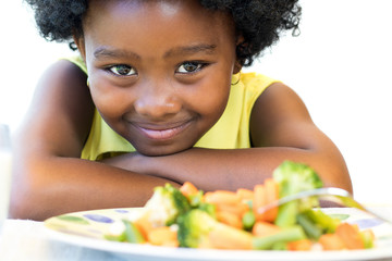 African girl in front of vegetable dish.