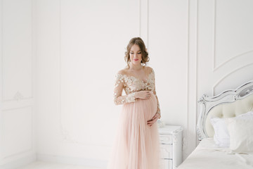 Pregnant woman in a white bedroom with New Year's decor